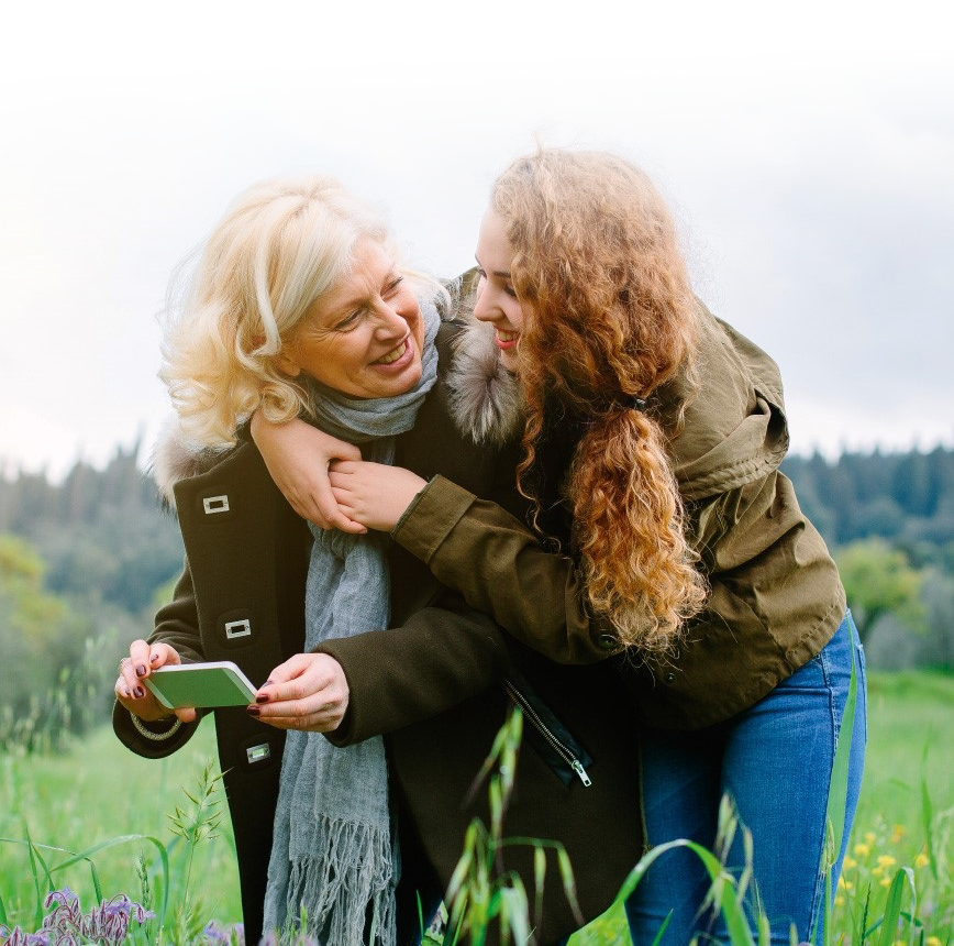 personal healthcare; grandmother and daughter hugging and smiling in a green field